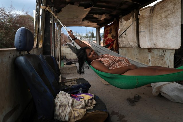 Venezuelan Belki Contreras relaxes on a hammock inside of an abandoned bus in the border city of Pacaraima, Brazil on April 13, 2019. Tens of thousands of migrants have fled the political and economic upheaval in Venezuela through Pacaraima, the only road crossing to Brazil, creating tension at the border. About 3.7 million people have left Venezuela in recent years, mostly via its western neighbor Colombia, according to the World Bank. (Photo by Pilar Olivares/Reuters)