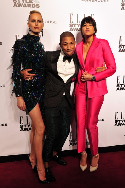 US singer Pharrell Williams (C) poses for pictures with his wife Helen Lasichanh (R) and Czech model Karolina Kurkova (L) as they attend the Elle Style Awards in central London, on February 18, 2014. (Photo by Carl Court/AFP Photo)