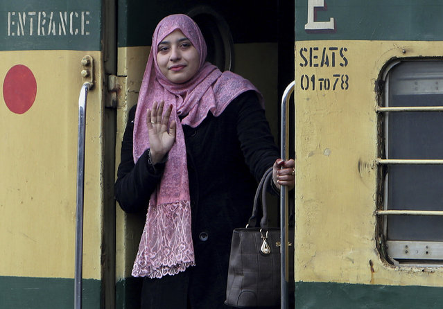 A passenger waves from the doorway of a train, on her way to India, after being stranded in Pakistan for a week, at Lahore Railway Station in Pakistan, Monday, March 4, 2019. A Pakistani railways official says a key train service between Pakistan and neighbouring India has been resumed, a sign on easing tensions between the two South Asian nuclear-armed rivals. (Photo by K.M. Chaudary/AP Photo)