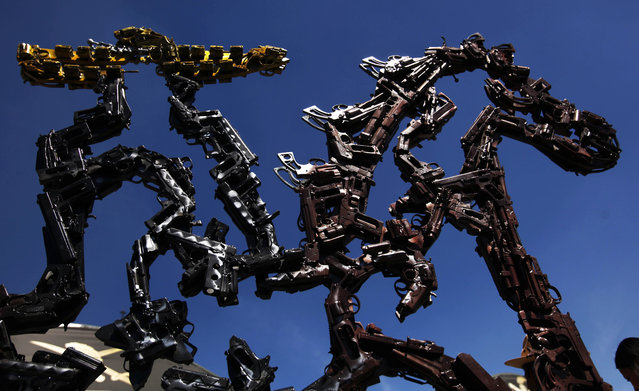"""A sculpture made from the parts of guns and other weapons titled """"Charro Jalisco"""" stands on exhibit in the Zocalo of Mexico City, Saturday, February 15, 2014. (Photo by Marco Ugarte/AP Photo)"""