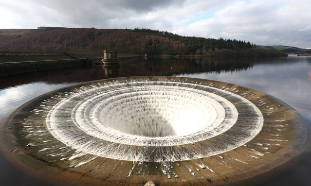 """Water flows down the  """"plughole"""" on the Ladybower Reservoir, one of two bell-mouthed 80ft wide stone overflows, on February 19, 2014. (Photo by Lynne Cameron/PA Wire)"""
