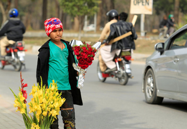 A boy holds a flowers bouquet for sale along a roadside on Valentine's Day in Islamabad, Pakistan, February 14, 2017. (Photo by Faisal Mahmood/Reuters)