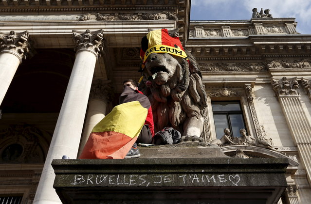 """A man wrapped in a Belgian flag sits next to a statue as people gather on the Place de la Bourse to pay tribute to the victims of Tuesday's bomb attacks in Brussels, Belgium, March 26, 2016. The writing reads, """"Brussels, I love you"""". (Photo by Francois Lenoir/Reuters)"""