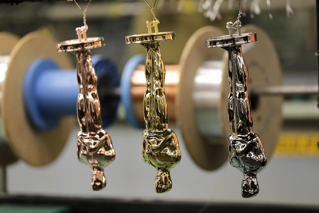 Oscar statuettes in various stages of the coating process are hung together at Epner Technology in the Brooklyn borough of New York, Tuesday, January 17, 2017. (Photo by Seth Wenig/AP Photo)