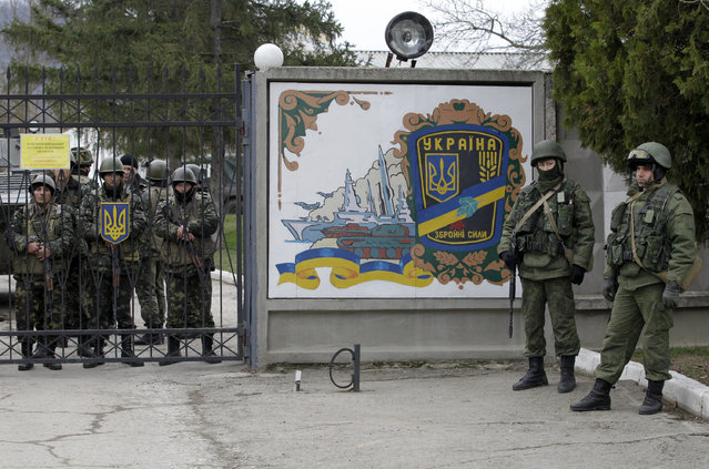 Ukrainian soldiers, left and unidentified gunmen, right, guard the gate of  an infantry base in Privolnoye, Ukraine, Sunday, March 2, 2014. (Photo by Darko Vojinovic/AP Photo)