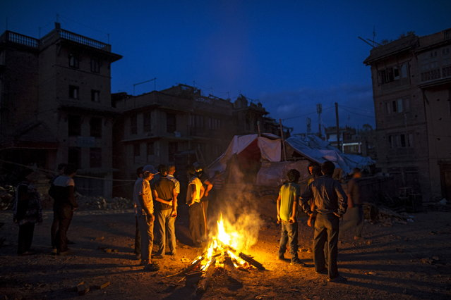 Local residents gather near a campfire in Bhaktapur, Nepal, May 12, 2015. (Photo by Athit Perawongmetha/Reuters)