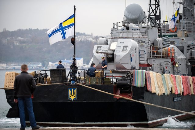 Ukrainian sailors work on board the Ukrainian navy corvette Ternopil as a Ukrainian Navy flag flies from the stern, at harbor in Sevastopol, Ukraine, Tuesday, March 4, 2014. Crimea still remained a potential flashpoint, as pro-Russian troops who had taken control of the Belbek air base in Crimea fired warning shots into the air Tuesday as around 300 Ukrainian soldiers, who previously manned the airfield, demanded their jobs back. (Photo by Andrew Lubimov/AP Photo)