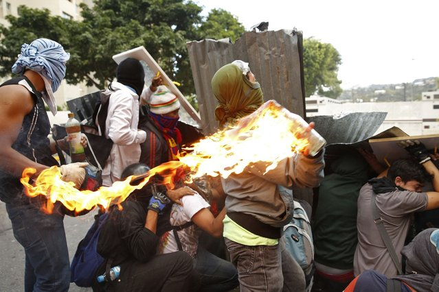 An anti-government protester throws a petrol bomb during clashes with police in Caracas, on March 2, 2014. (Photo by Carlos Garcia Rawlins/Reuters)