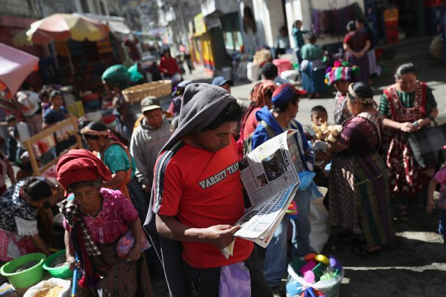 A vendor reads the newspaper at a vegetable market on February 11, 2017 in Almolonga, Guatemala. (Photo by John Moore/Getty Images)
