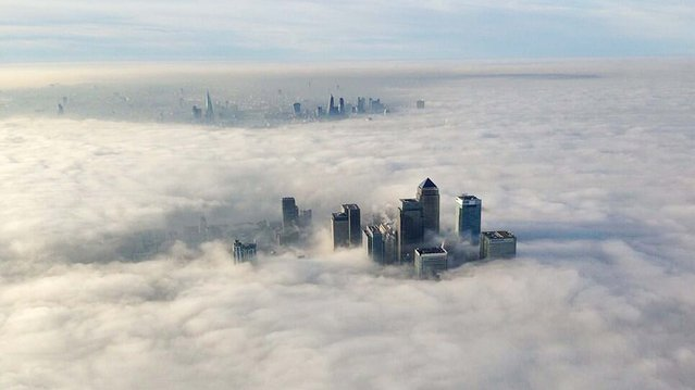 The Canary Wharf financial district (front) and central London emerge from morning fog in this aerial photograph released by the Metropolitan Police in London March 13, 2014. (Photo by Reuters/Metropolitan Police)