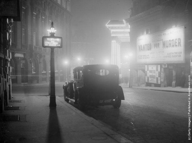 1936: A night scene in central London with an advertisement for the play Wanted for Murder
