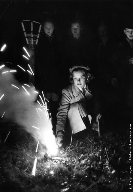 1952: A girl lights a firework at a Guy Fawkes night party, 1952