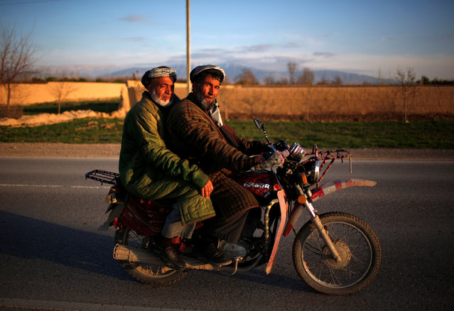 Afghan men dressed in traditional northern cloaks ride on a motorcycle in Mazar-I-Shariff, northern Afghanistan March 27, 2014. (Photo by Ahmad Masood/Reuters)