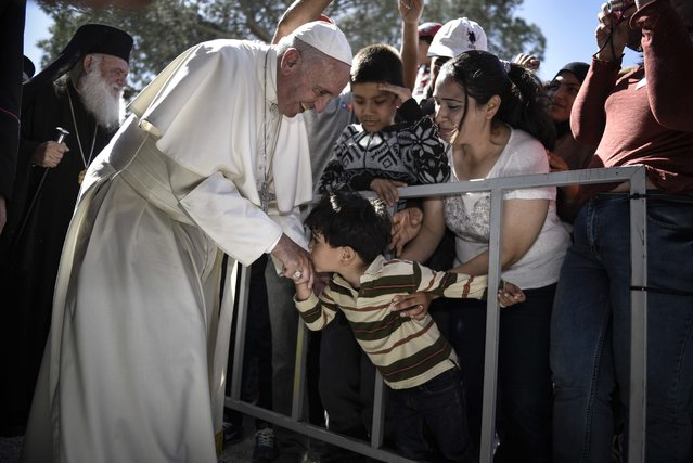 """In this photo released by Greek Prime Minister's office on Saturday, April 16, 2016, a child kisses the hand of Pope Francis, during a visit at the Moria refugee camp on the island of Lesbos, Greece.  Pope Francis implored Europe on Saturday to respond to the migrant crisis on its shores """"in a way that is worthy of our common humanity"""", during an emotional and provocative trip to Greece. (Photo by Andrea Bonetti/Greek Prime Minister's Office via AP Photo)"""