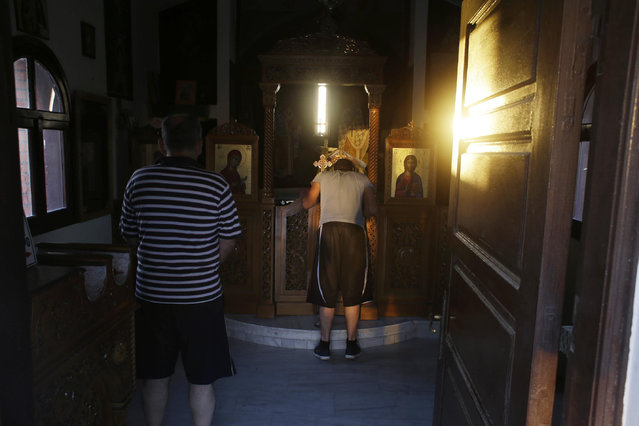 Syrian Christians John, 21, kisses an icon while his father Elias, 50, prays in a small Greek Orthodox church near the place where they arrived with dozens of other Syrians on a small boat from a Turkish coast to the Greek island of Lesvos on Wednesday, June 17, 2015. Around 100,000 migrants have entered Europe so far this year as Italy and Greece have borne the brunt of the surge with many more migrants expected to arrive from June through to September. (AP Photo/Thanassis Stavrakis)