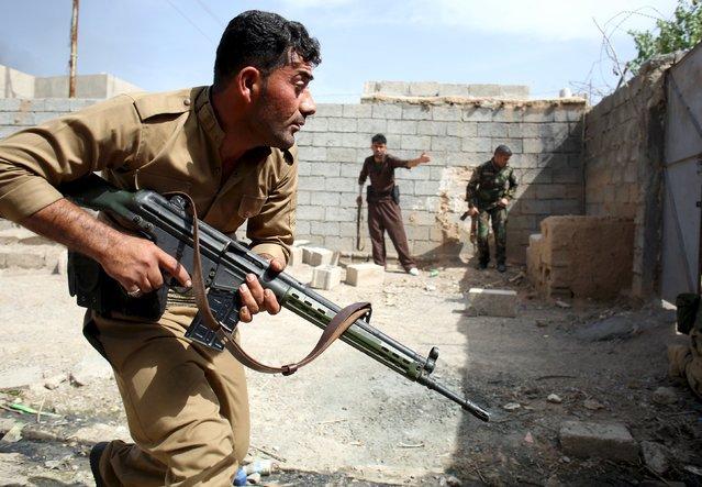 Kurdish gunmen search for Shi'ite militiamen during clashes in Tuz Khurmato, Iraq, April 24, 2016. (Photo by Goran Tomasevic/Reuters)