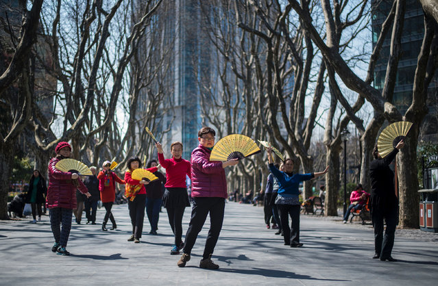 Women dance with fans in a park on a sunny day in Shanghai on March 15, 2017. (Photo by Johannes Eisele/AFP Photo)