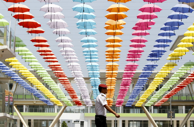 A security guard walks under the floating umbrella decorations at commercial business park in Rawang outside Kuala Lumpur, Malaysia Sunday, March 19, 2017. (Photo by Daniel Chan/AP Photo)