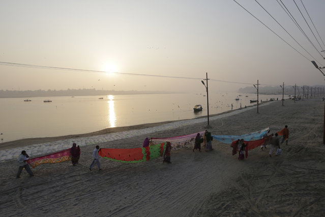 In this Thursday, January 5, 2017, file photo, Hindu devotees dry their clothes after taking a dip at Sangam, the confluence of rivers Ganges, Yamuna, and mythical Saraswati in Allahabad, India. (Photo by Rajesh Kumar Singh/AP Photo)