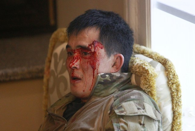 A member of Kyrgyz state security forces, who was injured during an operation to detain Almazbek Atambayev, lies on the floor in a house in the village of Koi Tash near Bishkek, Kyrgyzstan August 7, 2019. (Photo by Vladimir Pirogov/Reuters)