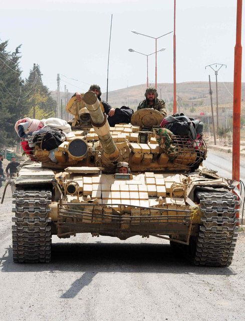 Syrian soldiers drive a tank in al-Sarkha village, in the Qalamun mountains, northeast of Damascus, after taking control of the village from rebel fighters, on April 14, 2014. Government forces took control of al-Sarkha in the morning before moving in to recapture the ancient Christian town of Maalula. (Photo by AFP Photo/STR)