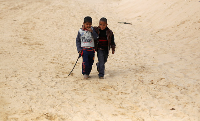 Faysal (L), a 7-year-old jockey, walks with his brother Amin during the opening of the International Camel Racing festival at the Sarabium desert in Ismailia, Egypt, March 21, 2017. (Photo by Amr Abdallah Dalsh/Reuters)