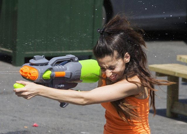 A woman takes part in a giant water fight on a hot summer day in central Brussels, Belgium, July 3, 2015. (Photo by Yves Herman/Reuters)