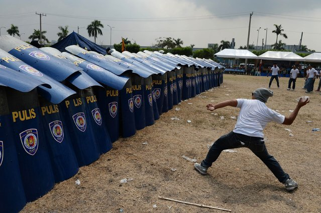 A mock protester throws a water bomb during police exercises to manage civil unrest in Manila on April 23, 2014 ahead of a visit by US President Barack Obama. The US leader plans to visit the Philippines on April 28-29. (Photo by Noel Celis/AFP Photo)