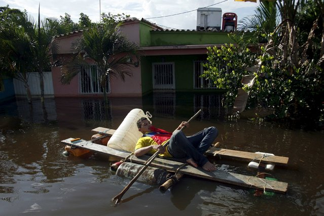 A man paddles a makeshift boat along a flooded street in Guasdualito, in the state of Apure, Venezuela, July 4, 2015. (Photo by Carlos Eduardo Ramirez/Reuters)