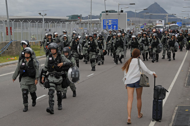 A passenger walks pass riot polices as protestors blocked a road outside the airport in Hong Kong, Sunday, September 1, 2019. Train service to Hong Kong's airport was suspended Sunday as pro-democracy demonstrators gathered there, while protesters outside the British Consulate called on London to grant citizenship to people born in the former colony before its return to China. (Photo by Kin Cheung/AP Photo)