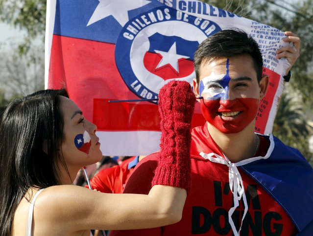 Chilean soccer fans paint their faces ahead of the Copa America 2015 final soccer match between Chile and Argentina in Santiago, Chile, July 4, 2015. (Photo by Rodrigo Garrido/Reuters)