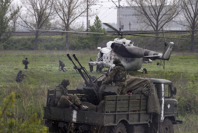 A Ukrainian military helicopter lands near a Ukrainian checkpoint near the town of Slaviansk in eastern Ukraine May 2, 2014. Ukrainian forces attacked the rebel-held city of Slaviansk before dawn on Friday and pro-Russia separatists shot down at least one attack helicopter, killing a pilot, in a sharp escalation of the conflict. (Photo by Baz Ratner/Reuters)