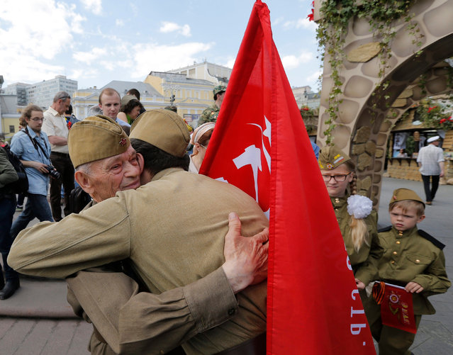 A man dressed in Soviet era-designed soldier uniform congratulates a WWII veteran (L) with a Victory Day after a military parade in the Red Square in Moscow, Russia, 09 May 2016. Russia celebrates the 71st anniversary of the victory over the nazi Germany in the World War II on 09 May. (Photo by Yuri Kochetkov/EPA)