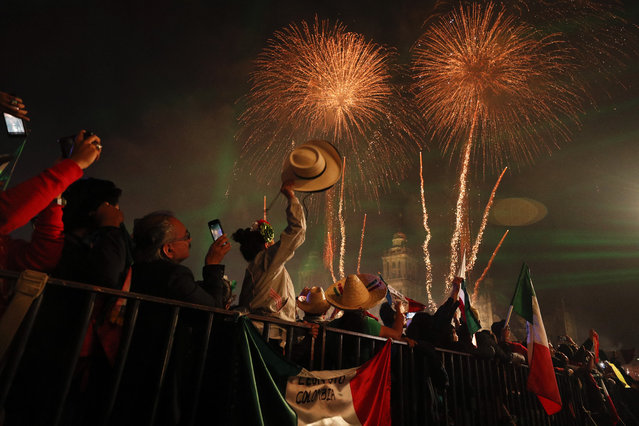"""Revelers celebrate as fireworks explode over the Metropolitan Cathedral after President Andres Manuel Lopez Obrador gave the annual independence shout from the balcony of the National Palace to kick off Independence Day celebrations in Mexico City, late Sunday, September 15, 2019. Every year the Mexican president marks the """"Grito de Dolores"""", commemorating the 1810 call to arms by priest Miguel Hidalgo that began the struggle for independence from Spain, achieved in 1821. (Photo by Rebecca Blackwell/AP Photo)"""
