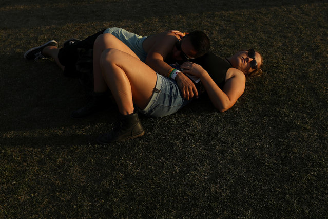 A couple sleep on the grounds during the Coachella Valley Music and Arts Festival on April 16, 2017 in Indio, California. (Photo by Carlo Allegri/Reuters)