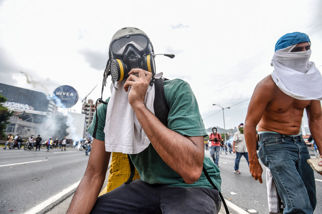 Demonstrators clash with the riot police during a protest against Venezuelan President Nicolas Maduro, in Caracas on April 20, 2017. (Photo by Juan Barreto/AFP Photo)