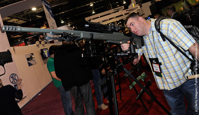 Nicholas Dugan of California looks at the new Tac-50 A1-R2 rifle on display at the McMillan Firearms Manufacturing booth