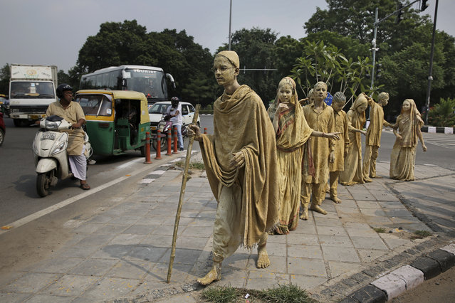 School children dressed up as statues, depicting Indian freedom leader Mahatma Gandhi's Dandi March, stand at a traffic intersection on the eve of Gandhi's 150th birth anniversary in New Delhi, India, Tuesday, October 1, 2019. Dandi March is the name given to the Salt Satyagraha (Salt March) where Gandhi and other freedom fighters marched 241 miles to the sea to make their own salt on April 6, 1930 as an act of civil disobedience against the British colonial rule. (Photo by Altaf Qadri/AP Photo)
