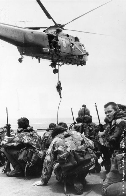 Waiting to be lifted by a Westland Sea King helicopter, Royal Marines from 40 Commando crouch on the flight deck of HMS Hermes, which heads the naval task force bound for the Falkland Islands