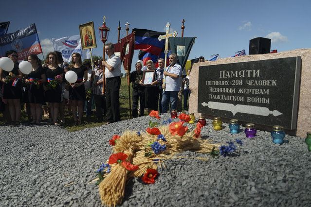 People stand with Orthodox crosses and icons as they attend a memorial service at the crash site of the Malaysia Airlines Flight 17, near the village of Hrabove, eastern Ukraine, Friday, July 17, 2015. In a solemn procession, residents of the Ukrainian village where a Malaysian airliner was shot down with 298 people aboard a year ago marched Friday to the crash site. (Photo by Mstyslav Chernov/AP Photo)