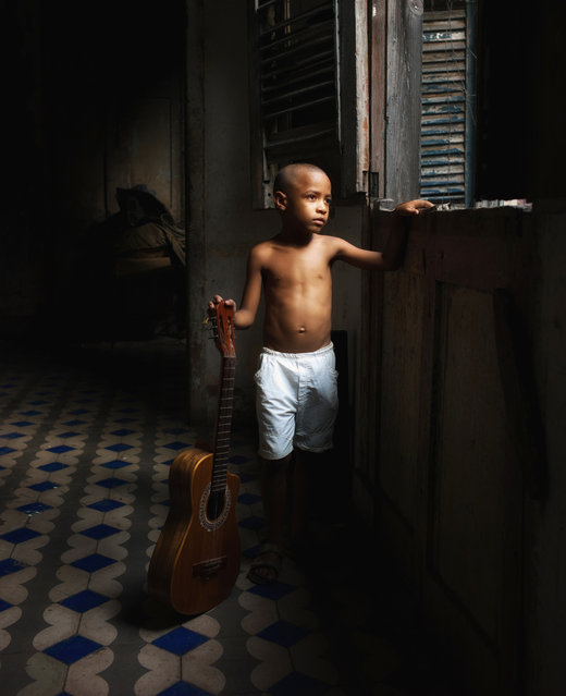 """The Cuban Boy"". A young boy looks out over the crumbling city of Havana. Photo location: Cuba. (Photo and caption by Simon Morris/National Geographic Photo Contest)"