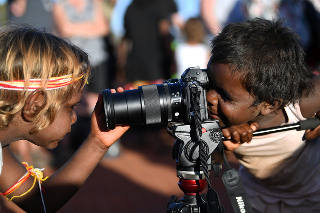 Indigenous Anangu children play with a camera during a ceremony marking the permanent ban on climbing Uluru, also known as Ayers Rock, at Uluru-Kata Tjuta National Park in Australia's Northern Territory on October 27, 2019. Indigenous Australians performed songs and traditional dance as the sun set over Uluru on October 27, capping a weekend of celebrations to mark the historic ban on climbing the sacred site. (Photo by Saeed Khan/AFP Photo)