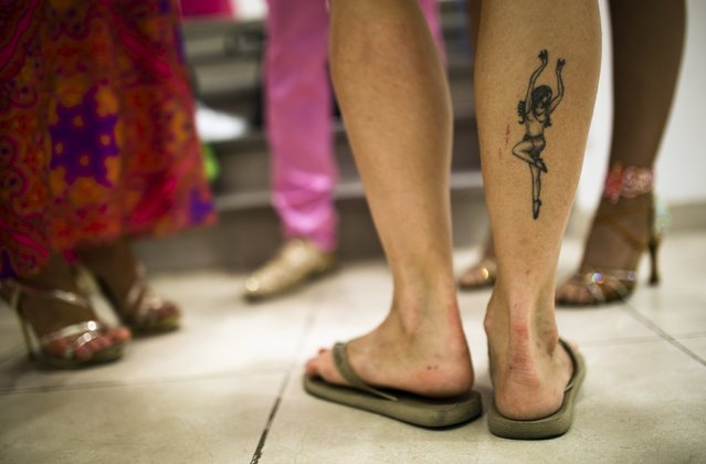 A tattoo on a person's calf is seen as participants stand backstage during a Latin dance competition in Tel Aviv, Israel July 18, 2015. (Photo by Amir Cohen/Reuters)