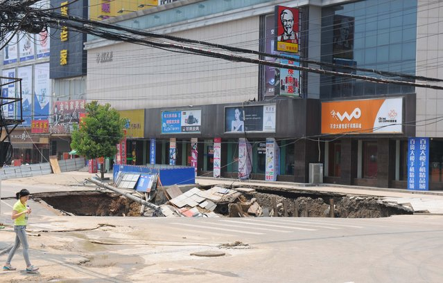 Over 100-squaremeter subsidence after road collapses is seen in front of a department store at Dingyuan County early morning on July 13, 2015 in Chuzhou, Anhui Province of China. The cave-in occurred on Monday in Anhui brought three people into injured and a truck trapped into the hole. The building near the collapse had closed down in case of joint collapse and further reasons were under investigation. (Photo by ChinaFotoPress/ChinaFotoPress via Getty Images)