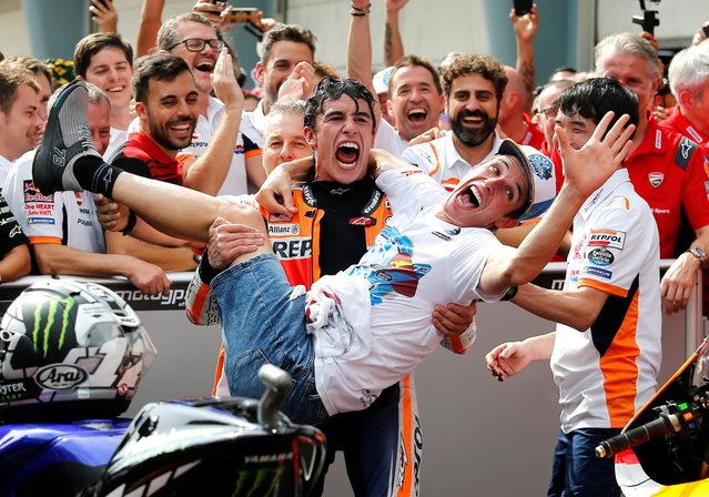 Spain's rider Marc Marquez, center, celebrates with his brother Spain's Moto2 rider Alex Marquez after winning the second place of MotoGP race at the Malaysia Motorcycle Grand Prix at Sepang International circuit in Sepang, Sunday, November 3, 2019. (Photo by Lai Seng Sin/Reuters)