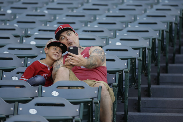 Nick Krist makes a funny face as he and his son, Noah, 8, take a selfie before a baseball game between the Los Angeles Angels and the Minnesota Twins, Wednesday, July 22, 2015, in Anaheim, Calif. (Photo by Jae C. Hong/AP Photo)