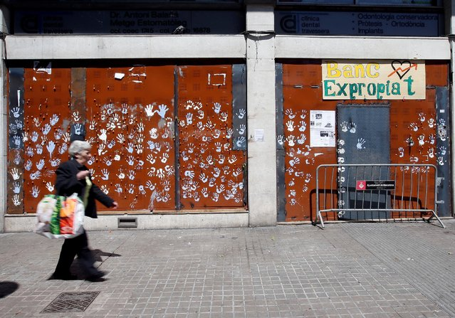 """A woman walks past """"The Expropriated Bank"""" which is at the center of protests in Barcelona, Spain, May 29, 2016. (Photo by Albert Gea/Reuters)"""