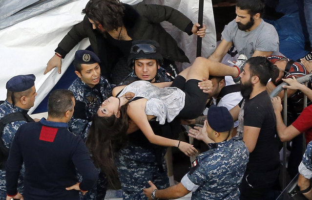 Riot police help an injured anti-government protester after scuffles broke out with women police officers on a road leading to the parliament building, during a protest in Beirut on November 19, 2019. Thousands of protesters rallying against the Lebanese political elite blocked roads in central Beirut on Tuesday, preventing lawmakers from reaching the parliament and forcing the postponement of a legislative session. (Photo by Bilal Hussein/AP Photo)