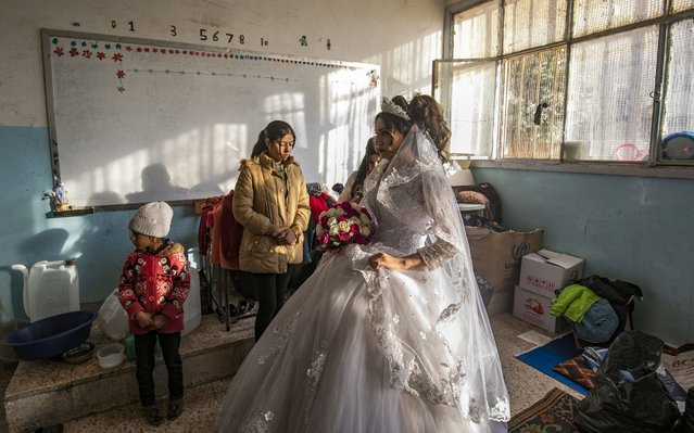 Hanan, a displaced Syrian woman wears her wedding dress at her temporary home, a school building transformed into a makeshift shelter, before being wed to Mohammad in the northern Syrian city of Hasakeh on December 1, 2019. Hanan and Mohammad fled with their families from the northeastern town of Ras al-Ain following the Turkish offensive against the Kurdish-dominated region, were wedded after being in love for three years. (Photo by Delil Souleiman/AFP Photo)