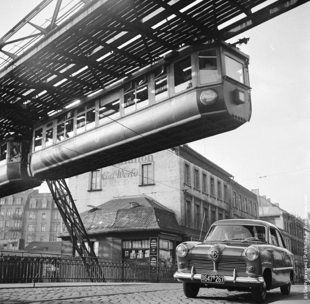 A hanging monorail train moves along the seven mile Wuppertal Monorail System in Germany, just over the path of the traffic, 1950